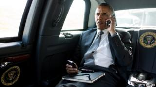 Barack Obama talks on the phone in his motorcade in July 2012