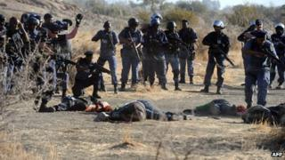 police aiming at miners laying on the ground after police opened fire during clashes near the Marikana platinum mine