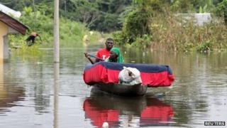 A man and his wife paddle a canoe with their belongings after flooding in the Amassoma community in Bayelsa state October 5, 2012.