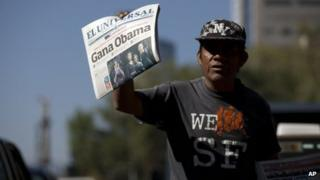 Newspaper vendor in Mexico City holds up newspaper that reads Obama Wins