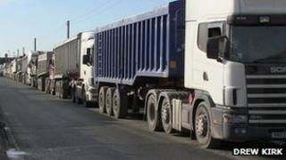 A queue of lorries on a single carriageway road