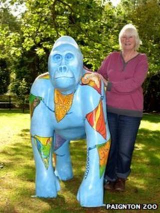 """Devon artist Sue Misselbrook with """"Herbert"""" gorilla, featuring flags with African designs"""