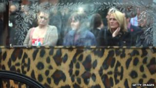 The leopard-print coffin leaves the Church of the Resurrection in Ely, Cardiff