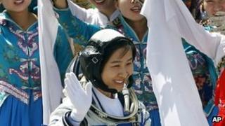 China's first female astronaut Liu Yang waves during a sending-off ceremony as she departs for the Shenzhou 9 spacecraft rocket launch pad (16 June 2012)