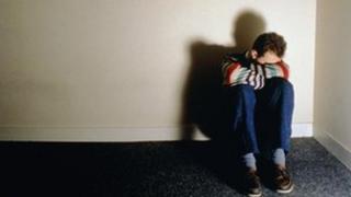 Youth sitting in corner