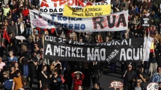 Demonstrators hold banners protesting the visit to Portugal of German Chancellor Angela Merkel, Lisbon, 12 Nov