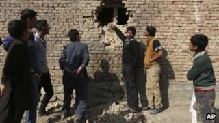 Afghan men look at a hole in the wall of a house caused by a rocket attack in Kabul November 13, 2012