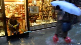 A man sits in his shop as a passer-by wades through a flooded street in Venice, 11 November 2012