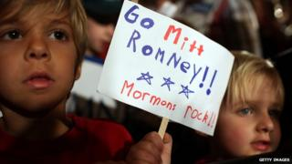 """Two children at a Mitt Romney rally in South Carolina, holding up a sign that says """"Go Mitt Romney: Mormons rock"""""""