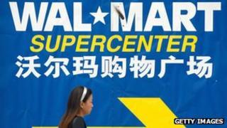 A pedestrian walks past a Wal-Mart signboard in Beijing