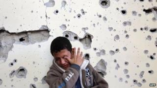 Palestinian boy cries as he sits outside his home which was damaged following an Israeli air strike