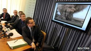 Members of Poland's Internal Security Agency (AWB) and the Prosecutors' Office sit in front of a screen showing evidence of a planned attack, during a news conference in Warsaw