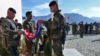French soldiers fold their flag during a handover ceremony at the French military Camp Nijrab in Nijrab district of Kapisa province on November 20, 2012.