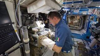 Italian astronaut Paolo Nespoli conducting experiments on the space station
