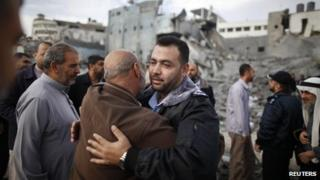 A Hamas police officer is hugged by a Palestinian man after they returned to their destroyed police headquarters in Gaza City November 22, 2012