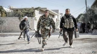 Rebels defending the town run towards a forward fighting position in Maraat al-Numan November 20, 2012