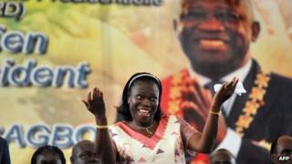 Simone Gbagbo dances under a portrait of her husband, during a meeting in his support on 15 January 2011 in Abidjan