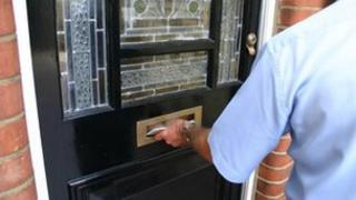 Postman putting letter through a letter-box