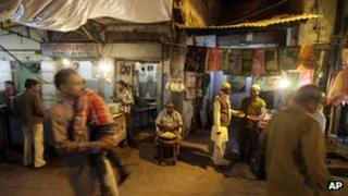 People walk past stalls at the entrance to Nizamuddin Dargah, a complex of tombs, mosques and stalls centered on the burial site of revered Sufi saint Nizamuddin Auliya, in New Delhi, India, Tuesday, Nov. 20, 2012.