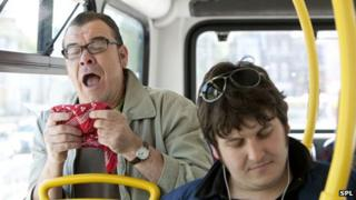 Man sneezing on a bus