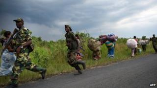 M23 rebels run towards the town of Sake, 26km west of Goma, as thousands of residents flee fresh fighting in the eastern Democratic Republic of the Congo town on November 22, 2012