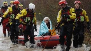 Woman being rescued from flood water
