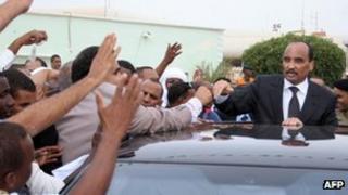 President Abdelaziz waves to crowds