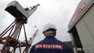 Workman standing in the Govan shipyard in Glasgow, owned by BAE Systems