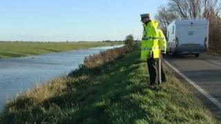 Fire officer and police at scene of river death
