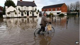 A man wheels his bike through floodwaters in Tewkesbury