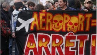 "Demonstrators hold a banner saying ""Airport, Stop"" at a demonstration on Saturday"