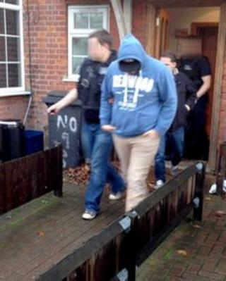 Suspect being led away by police officers after being arrested in Mill Hill