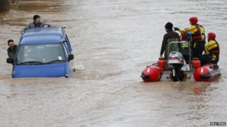 Rescue crews in a dingy pass a van driving along a flooded street in Gloucester