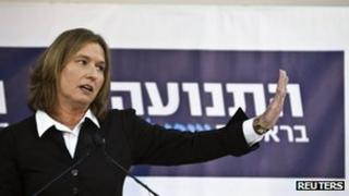 Tzipi Livni addresses journalists in front of the banner of her new party