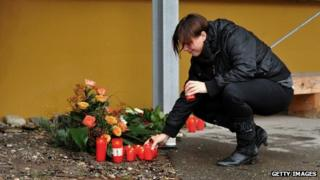 A women lights a candle at a Caritas employment facility for the handicapped where a fire killed 14 people on November 27