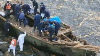 Police officers investigating a wooden boat with Korean language markings on Sado island, Niigata City, on 28 November 2012