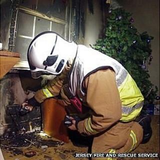 Firefighter inspects Damage caused by fire in St Helier flat