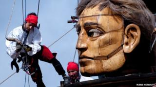 """Dozens of people work the ropes of """"The Giants"""" to operate them."""