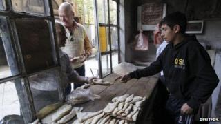 Men buy bread in the old city of Damascus on 8 November