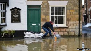 Man scooping water away from property