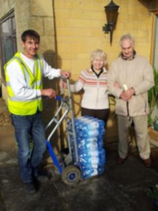 Ken and Patricia Smith take a delivery of water at their Broadway home