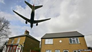 A passenger jet flies over rooftops as it prepares to land at Heathrow airport in west London