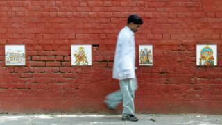 Images of Hindu gods protect a wall from urinaters