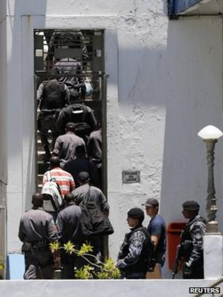 Arrested police officers arrive at their headquarters in Rio de Janeiro