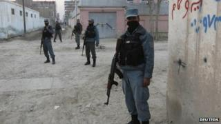 Afghan policemen stand guard near the site of a suicide attack that wounded Mr Khalid