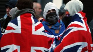 Loyalists in flags and face masks