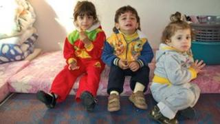 Three small children of Maimoun, a Palestinian refugee, seated on a mattress in their room at Cyber City camp