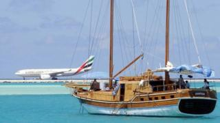 In this file picture taken on October 18, 2003, an aeroplane lands at Male International Airport while a sail boat makes its way through a blue lagoon.