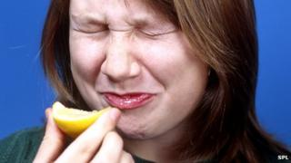 Woman biting into a lemon
