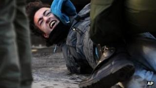 Greek riot police detain a protester in Thessaloniki, 6 December